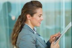 使用片剂个人计算机的愉快的女商人 免版税库存照片