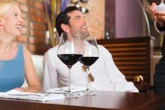 耦合在餐馆或棒的饮用的红葡萄酒 图库摄影