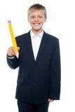 拿着巨型大小的黄色铅笔的男孩 库存照片