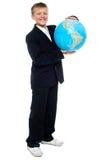 聪明的看起来的小孩藏品地球 免版税库存照片