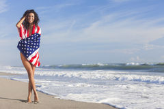 Προκλητικό νέο κορίτσι γυναικών στη αμερικανική σημαία στην παραλία Στοκ Εικόνες