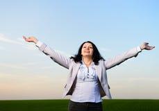 Μια γυναίκα σε ένα επιχειρησιακό κοστούμι με τα χέρια τους που αυξάνονται Στοκ εικόνα με δικαίωμα ελεύθερης χρήσης
