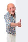 愉快的微笑的老人拿着一个空白董事会 免版税库存图片