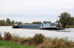 拖曳小船在荷兰语河扯拽无舵的货轮 免版税库存照片