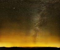 在黑色山和城市光的银河 库存图片