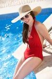 妇女坐边缘游泳在池 免版税库存照片