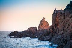 日出轻发光在礁石岩石 图库摄影