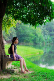 Το χαριτωμένο ταϊλανδικό κορίτσι κάθεται μόνο κοντά στον ποταμό β Στοκ Εικόνες