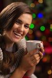 享用杯子热巧克力的愉快的少妇 免版税图库摄影
