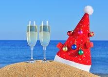 杯香槟和在海滩的圣诞老人帽子 免版税库存图片
