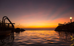 无限与海运的边缘池在日落之下 免版税库存照片