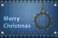 在蓝色牛仔裤背景的圣诞节问候 库存图片