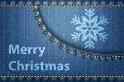 在蓝色牛仔裤背景的圣诞节问候 库存照片