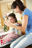 排序洗衣店的母亲和女儿 免版税库存照片