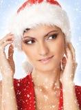 一名可爱的妇女的纵向圣诞节帽子的 免版税库存照片