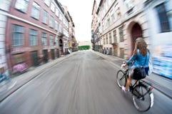 快速地乘坐的自行车的女孩 免版税库存照片