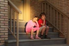 兄弟和姐妹坐台阶在门附近 库存照片
