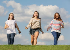 三个微笑的女孩运行在草 库存照片