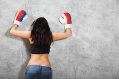 拳击手套的女孩倾斜对墙壁 库存照片