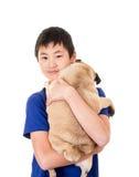 拿着他的狗的青少年的男孩 免版税库存照片