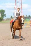 美丽的幼小白肤金发的妇女骑马栗子马 免版税库存图片