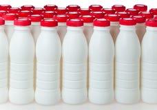 Μπουκάλια γιαουρτιού με τις κόκκινες καλύψεις Στοκ Εικόνες