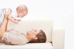 放置在沙发的母亲和婴孩 免版税库存图片
