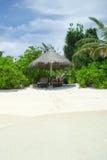 在田园诗沙子的海滩睡椅和伞靠岸 库存照片