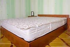 与轻便短大衣的河床床垫。 卧室内部 免版税图库摄影