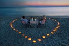 一对新夫妇共享在海滩的一顿浪漫正餐 免版税图库摄影