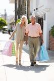 高级夫妇运载的购物袋 库存图片
