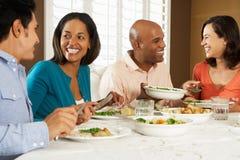 Группа в составе друзья наслаждаясь едой на дому Стоковые Изображения RF