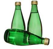 在白色背景隔绝的三个绿色玻璃瓶 免版税库存照片