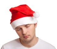 圣诞老人帽子的年轻人 免版税库存照片