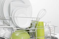 烘干在碗架的绿色和空白盘 免版税库存照片