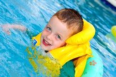 与救生背心的小男孩游泳 图库摄影