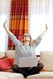 有膝上型计算机的可爱的妇女在家 免版税库存照片