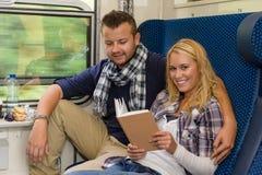 旅行通过培训妇女读取微笑的夫妇 库存图片