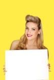 有一个空白符号的迷人的白肤金发的妇女 图库摄影