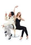 交谈者和芭蕾舞女演员坐椅子和姿势 免版税库存图片