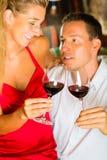 男人和妇女分派任务在地窖里喝酒 免版税库存照片