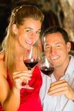 男人和妇女分派任务酒在地窖里 免版税库存照片