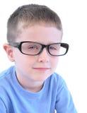 戴眼镜的聪明的小男孩在白色 免版税库存图片