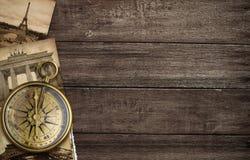 有老明信片的黄铜古色古香的指南针 库存照片