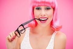 戴桃红色假发和眼镜的妇女 免版税库存图片