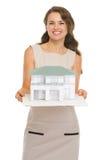 Γυναίκα αρχιτεκτόνων που εμφανίζει μοντέλο κλίμακας του σπιτιού Στοκ Εικόνες