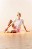 美丽的芭蕾舞女演员坐握脚腕的楼层 免版税库存照片