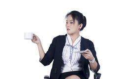 坐在与一杯咖啡的办公室椅子的女商人 库存照片