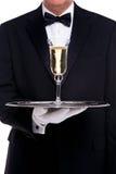 供食一杯香槟的男管家 免版税库存照片
