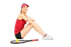 休息在符合以后的一个微笑的女性网球员 库存图片